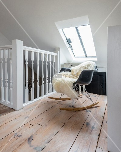 Moderner Schaukelstuhl mit Schaffell unter dem Dachfenster