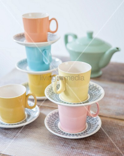 Pastel retro tea set stacked on rustic wooden table