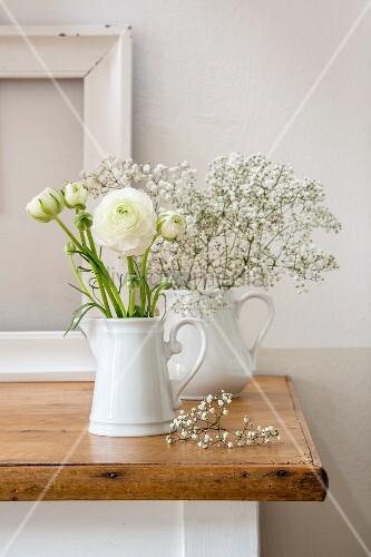 Ranunculus and gypsophila in two white milk jugs