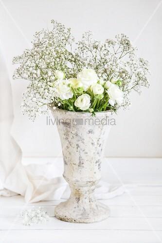 weiße Ranunkeln und Schleierkraut in einer Steinvase