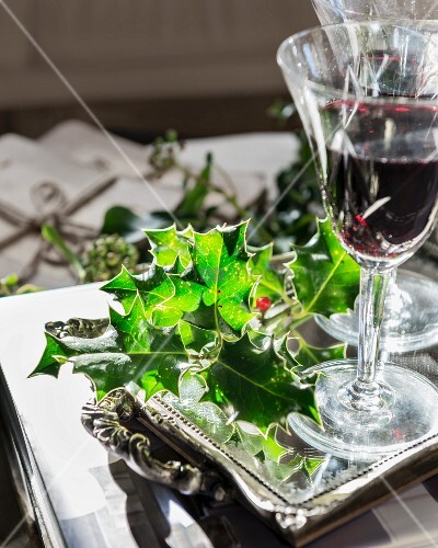 Sprig of holly and glasses of red wine on mirrored tray