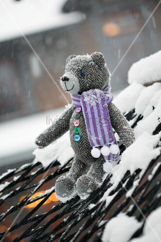 Tweed teddy bears wearing scarf sitting on snowy hammock