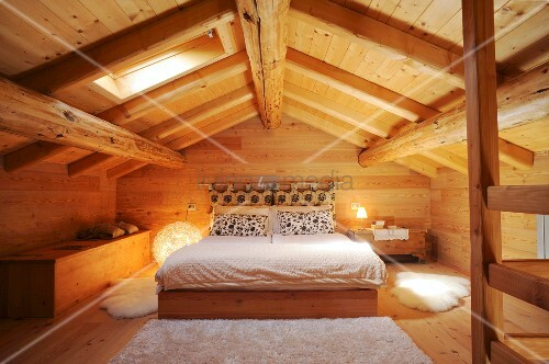 Attic bedroom in wooden house
