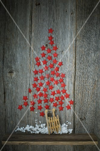 Christmas tree made from red stars on wooden wall