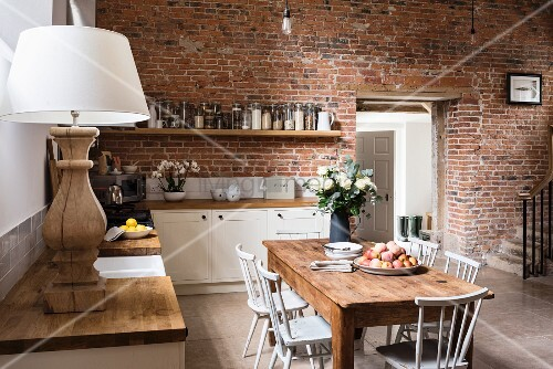Rustic wooden table in open-plan kitchen with brick wall
