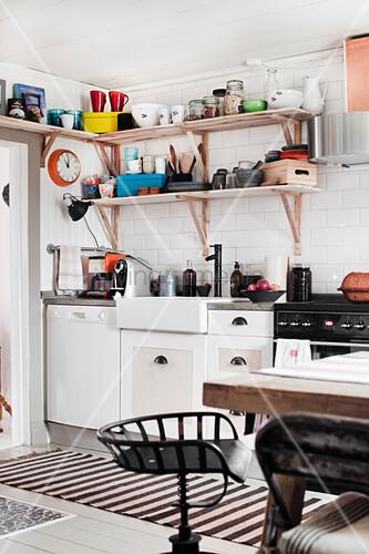 Metallstuhl in einer Landhausküche mit offenen Regalen