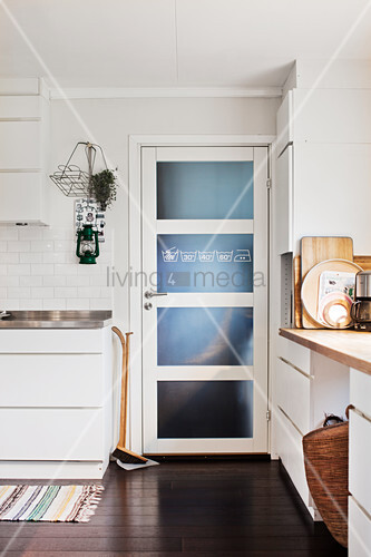 Dustpan and brush next to door with glass panels in white kitchen