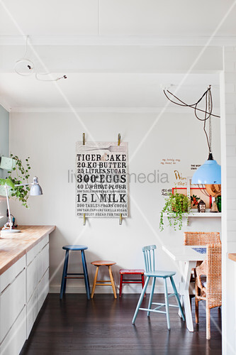 Colourful stools in white kitchen with dark wooden floor