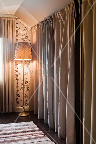 Floor-length curtains screening dressing room and standard lamp in bedroom