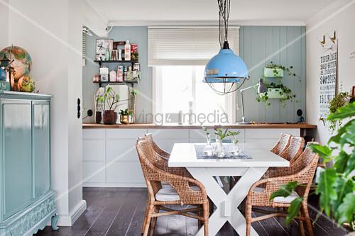 Weißer Esstisch mit Rattanstühlen und hellblau lackierte Kommode mit Türen in offenem Wohnraum