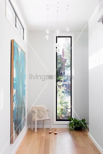 Heller Flur mit Armlehsntuhl vor schmalem Fenster, türkisfarbenes Bild an der Wand