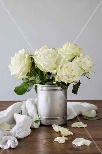 Strauß mit weißen Rosen in einer alten Silberdose