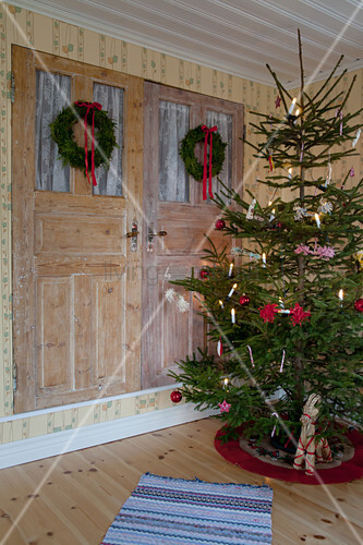 Simply decorated Christmas tree next to fitted cupboards with two wreaths on doors