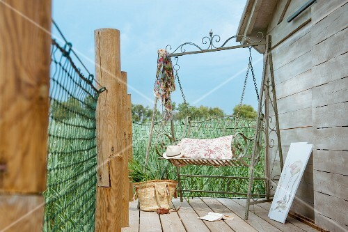 Romantic, ornate metal garden swing bench on terrace