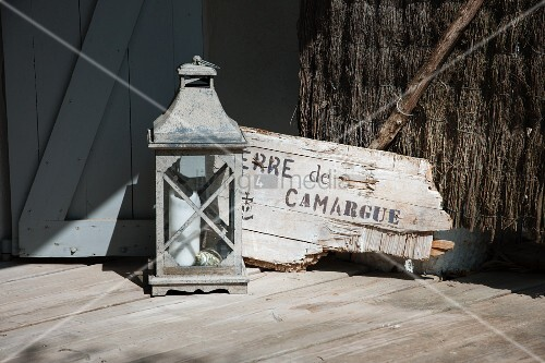 Candle lantern next to piece of driftwood with lettering