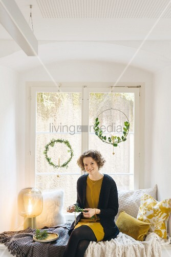 Woman making hand-made Christmas dreamcatchers with two hung in window