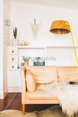 Helle Ledercouch mit Felldecke und Stehlampe vor Sideboard