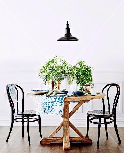 Runder rustikaler Tisch mit schwarzen Kaffeehausstühlen