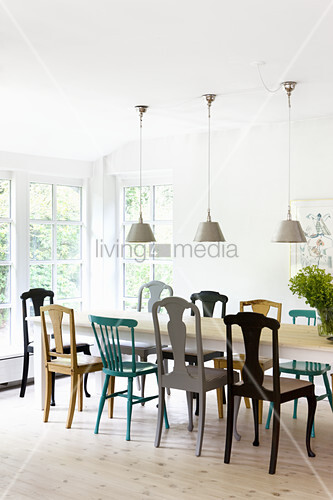 Three ceiling lamps above dining table and various brightly coloured chairs