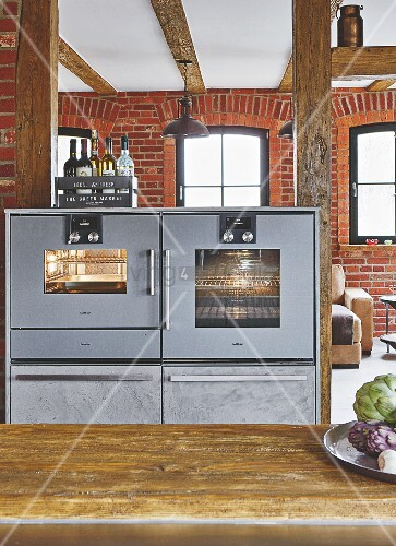 An oven and a steam cooker in a kitchen with a brick wall
