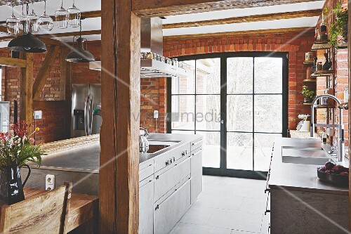 An island in front of a terrace door in a kitchen with exposed brickwork and wooden pillars