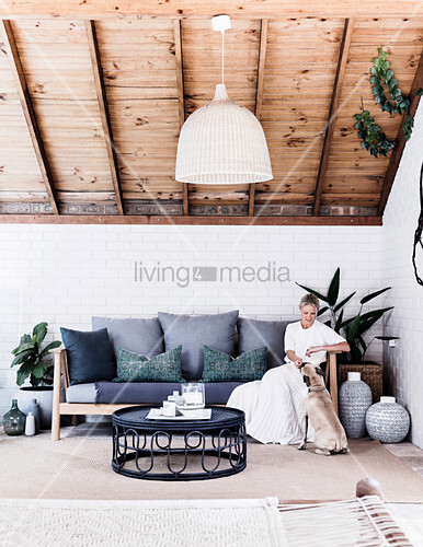 Frau und Hund auf überdachter Terrasse mit Sofa, Coffeetable und Holzdecke
