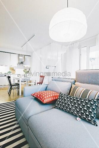 Graue Polstersofa mit Kissen auf schwarz-weiss gestreiftem Teppich, in hellem, offenem Wohnraum