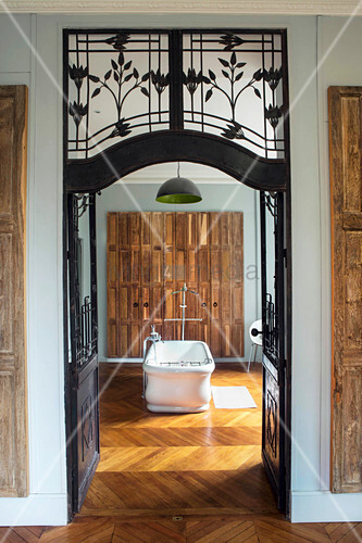 View through wrought iron and glass door into bathroom with free-standing bathtub