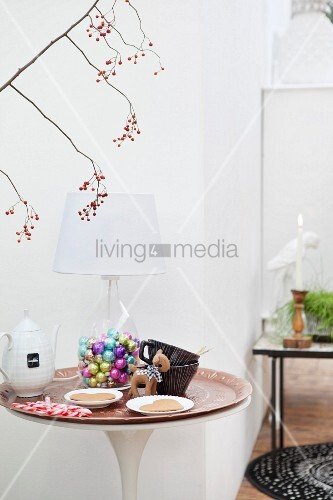 Glass bottle filled with colourful Christmas baubles used as base for table lamp