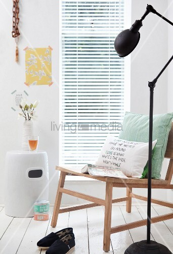 Hand-made cushion cover with motto on wooden chair next to standard lamp
