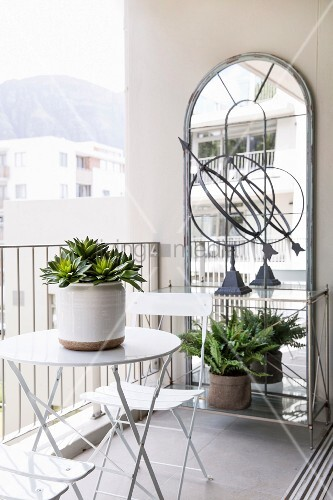 Bistro table and chairs in front of large wall-mounted mirror on balcony