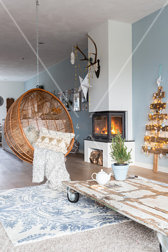 Hanging chair in front of fireplace in living room with blue wall
