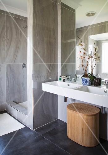 Elegantes Bad mit Duschbereich und weißem Doppelwaschbecken