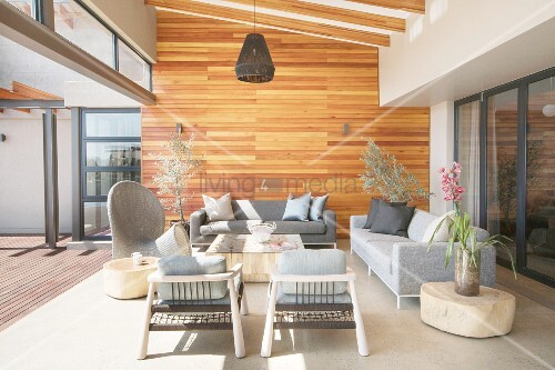 Designer furniture in shades of grey and wood-clad wall on veranda