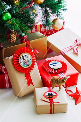 Verpackte Geschenke mit Foto-Anhängern und Rosetten