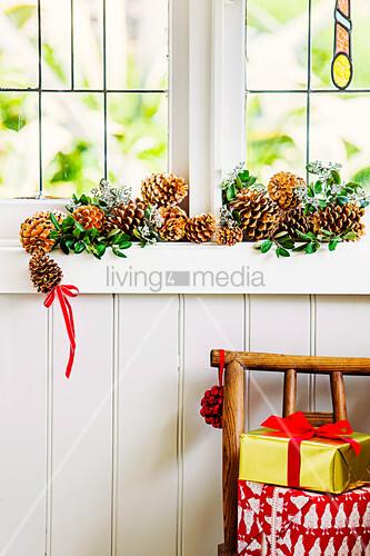 Girlande aus Zapfen und Blätterzweigen am Fenstersims