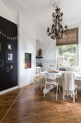 Recessed fireplace, black accent wall and wooden floor in dining room