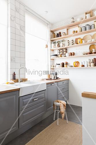 Wandregale mit Küchenaccessoires in Brauntönen in grauer Küche