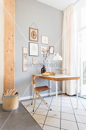 Bildergalerie an grauer Wand hinter dem Schreibtisch im Retrostil