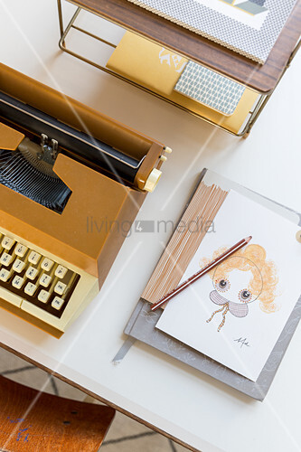 Postcard and notebook next to old typewriter