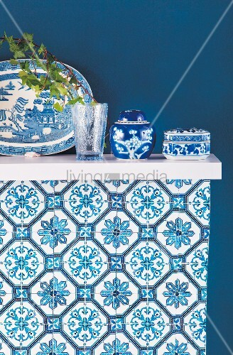 Blue and white Oriental china on shelf mounted on blue wall
