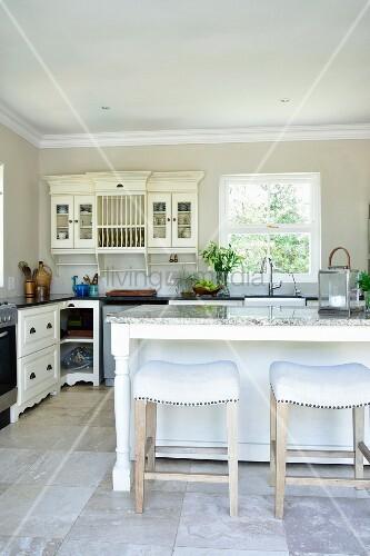 Weisse Hocker und Kücheninsel, im Hintergrund Wandschrank neben ...