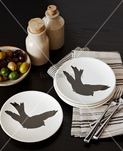 weiße Teller mit schwarzen Vögeln auf gestreiften Servietten