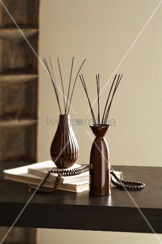 Brown vases with perfume diffusers on table