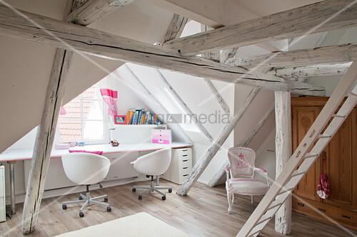 Schreibtisch unter dem Fenster im Dachzimmer mit weißen Balken