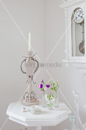 Kerzenhalter aus Wellpappe auf einem weißen Tischchen