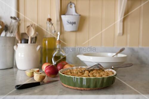 Äpfel und Kuchen in der Terrine auf der Marmorplatte in der Küche