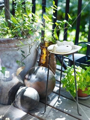 Steinkugel, Pflanzgefäß, Metallgestell und gesammeltem Strandgut auf Balkon