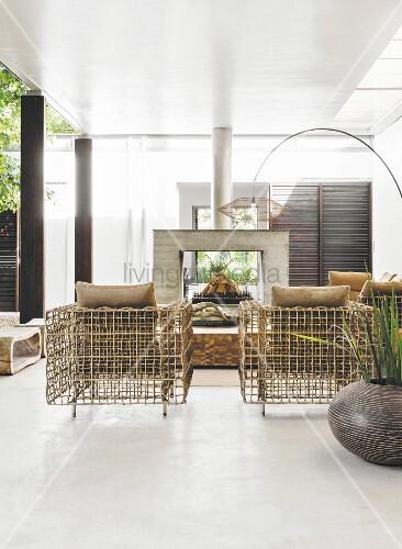 Designer-Rattanmöbel in Wohnraum mit Kamin und Bogenleuchte