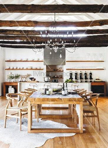 Classic chairs and rustic wooden beams in dining area in front of open-plan kitchen